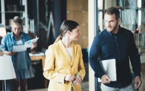Two workers walking through office space